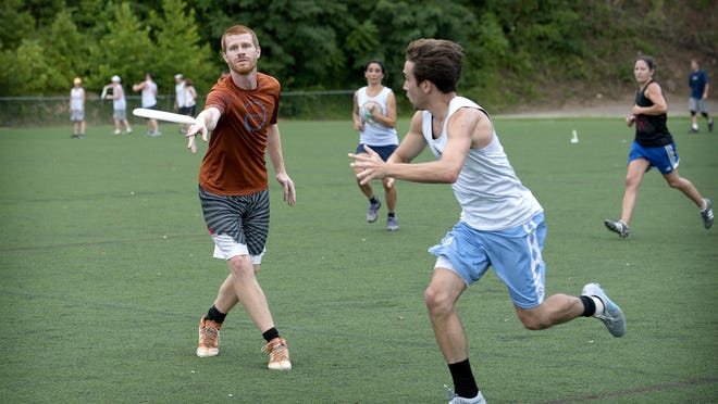 Matt Glenn throws a pass as Jesse Kovacs runs to attempt to block as the Seven Deadly Sins take on Jurassic Mark in an Asheville Ultimate Club game at Memorial Stadium on July 29. The club is hosting a regional tournament, the Hodown XIX, Aug. 15 and 16.
