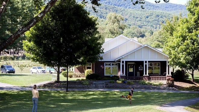 A teenage girl in group foster care plays catch with Cameron Templin, 8, a house parent's son, at the Black Mountain Home for Children . Foster kids live in one of four cottages on the main campus with other children and house parents.