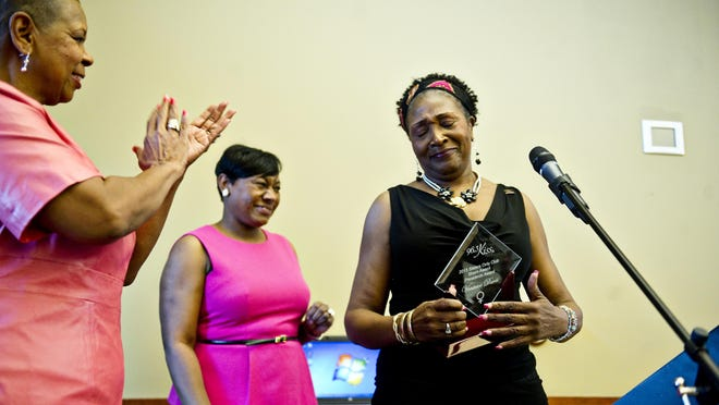 Joyce Epps-Watkins (left), first vice president of Cher's Sisters Only Club, and Cher Best (center), president, applaud as Vonteice Davis receives the President's Award at the seventh annual SHERO Awards in 2013.