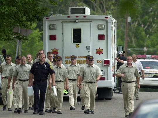 Police academy personnel walk along Grange Hall Road near Route 11 in Kirkwood on July 5, 2002.