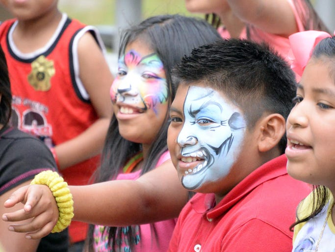 Flor Hernandez, 10 (center), and her brother Alex Hernandez, 9, of Vineland, were all smiles after having their faces painted during the Puerto Rican Festival at Landis Park in Vineland on Thursday, July 24, 2014.  Staff photo/Charles J. Olson