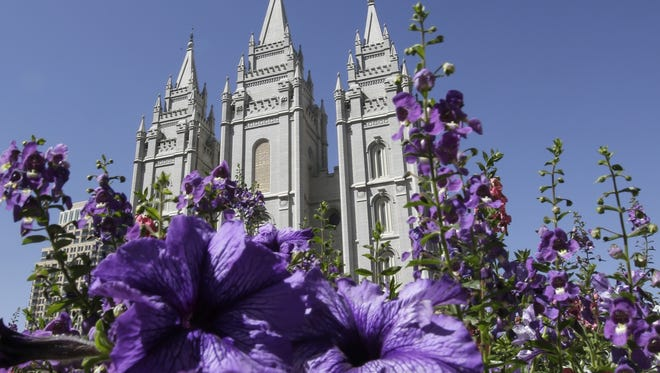 In this Sept. 3, 2014, file photo flowers bloom in front of the Salt Lake Temple, at Temple Square, in Salt Lake City.