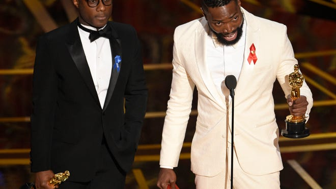 Barry Jenkins, left, and Tarell Alvin McCraney accept the award for best adapted screenplay for 'Moonlight' at the Oscars on Sunday.