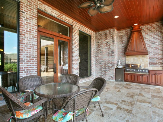 The outdoor kitchen and living areas overlook the gardens and pool.