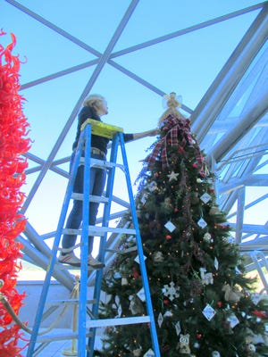 "Mary Maxson putes the finishing touches on a ""giving tree"" to benefit the Old Mill. The tree is on display in the lobby of the Spencer Theater next to a glass sculpture by Dale Chihuly."