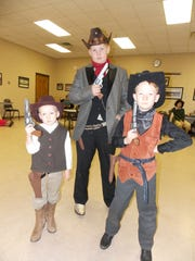 "Homeschool Performing Arts Club actors Adam Streeter, left, Colin Streeter and Jimmy Streeter pose with their props during a rehearsal of of ""How the West was Dun, or Left High and Dry in Low Humidity Chasm."""