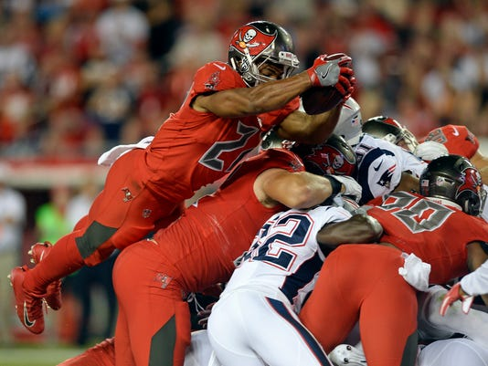 Tampa Bay Buccaneers running back Doug Martin, left, dives over the New England Patriots defense for a 1-yard touchdown during the first half of an NFL football game, Thursday, Oct. 5, 2017, in Tampa, Fla. (AP Photo/Jason Behnken)