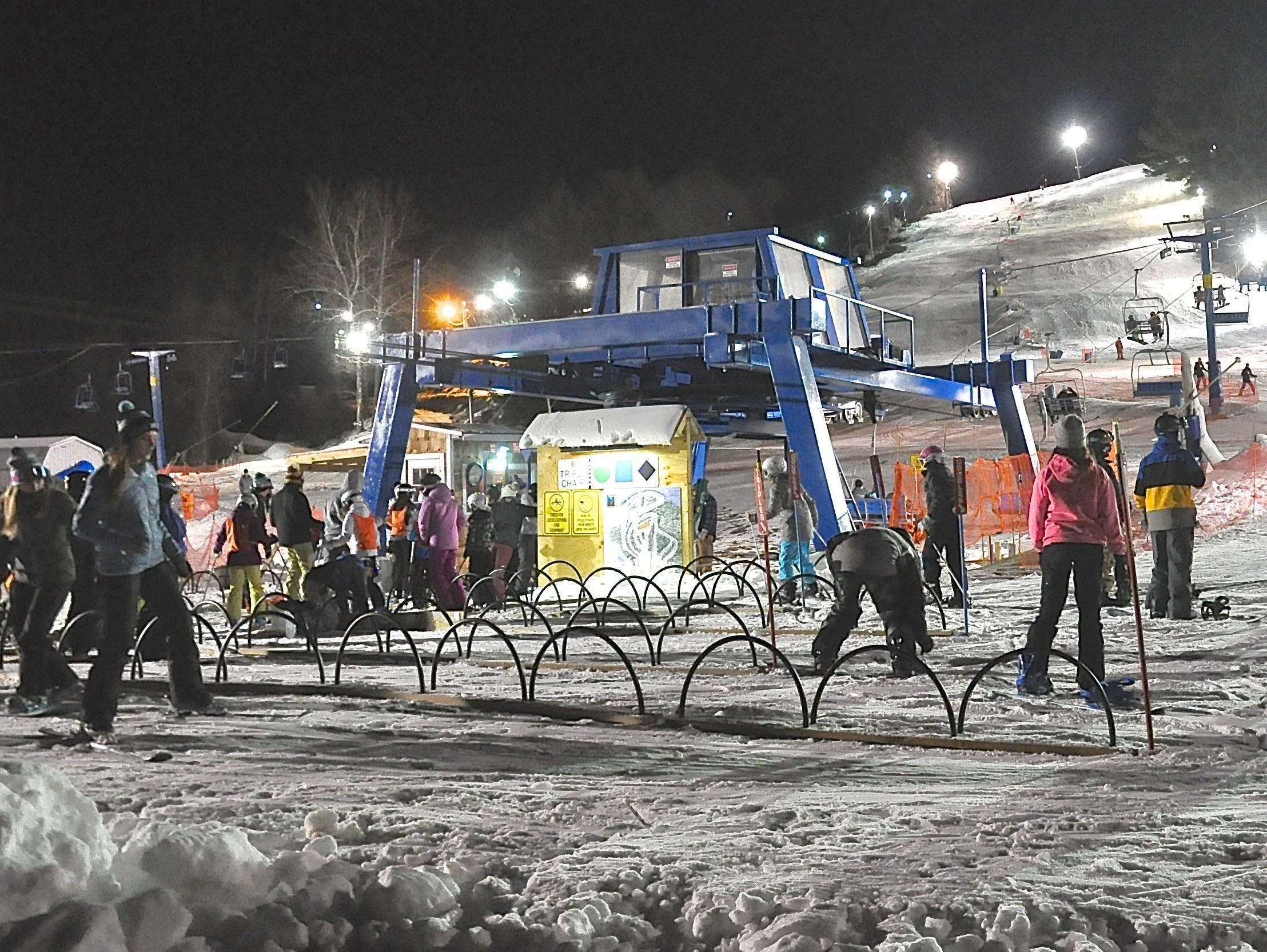 Skiers and snowboarders wait to ride a lift at Thunder Ridge Thursday night..