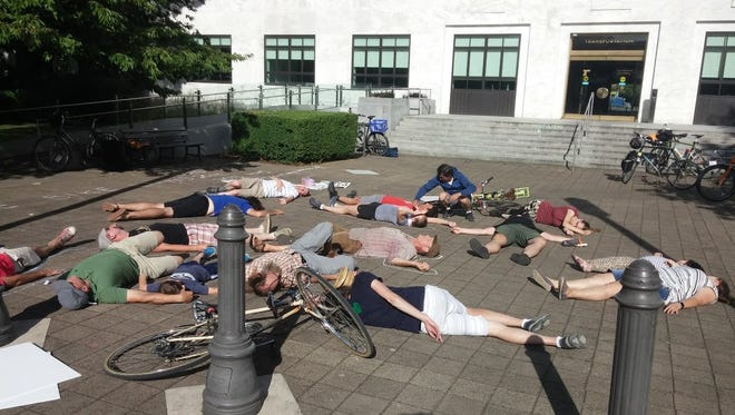 Bike activists stage a die-in near the entrance of the Oregon Department of Transportation building on Saturday, July 16, 2016.