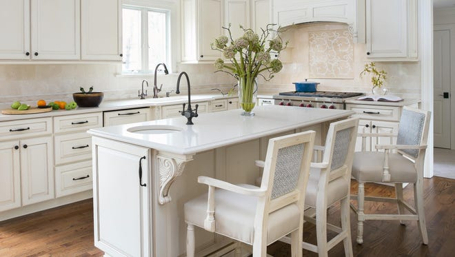 Transitional design in this open floor plan combines the best of traditional and contemporary design. Painted beige cabinets with chocolate glazing create a soft and peaceful mood. This state-or-the-art kitchen works perfectly for this busy family of five and a gourmet cook.