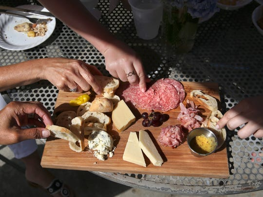The group enjoys the Finger Lakes Meat and Cheese Board at Heron Hill Winery during a food crawl around Keuka Lake on Monday, Aug. 7, 2017.