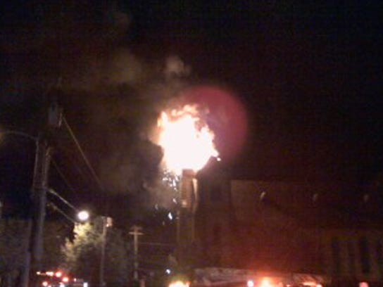 Flames shoot from the steeple of the College Street