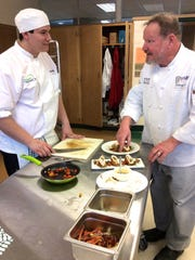Tom Surwillo (right) gives advice to one of the members of Greendale High School's ProStart culinary competition team.