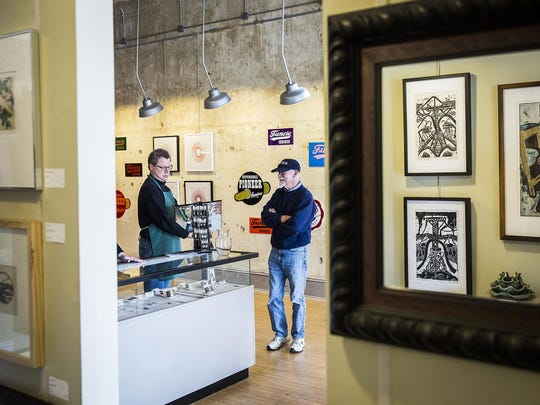 Co-owner Carl Schafer works with a customer at Gordy Fine Art and Framing Co.