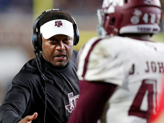 Texas A&M head coach Kevin Sumlin congratulates defensive lineman Jarrett Johnson (40) for helping stop Mississippi from getting a first down during the second half of an NCAA college football game in Oxford, Miss., Saturday, Nov. 18, 2017. Texas A&M won 31-24. (AP Photo/Rogelio V. Solis)