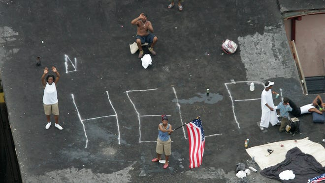 Residents wait on a rooftop to be rescued from the floodwaters of  Hurricane Katrina in New Orleans. Dozens of lawsuits seeking damages from the federal government for Hurricane Katrina-related levee failures and flooding in the New Orleans area are over. U.S. District Judge Stanwood Duval Jr. has dismissed the cases. The move comes more than a year after a federal appeals court overturned his ruling that held the U.S. Army Corps of Engineers liable for flooding caused by lax maintenance of a shipping channel.