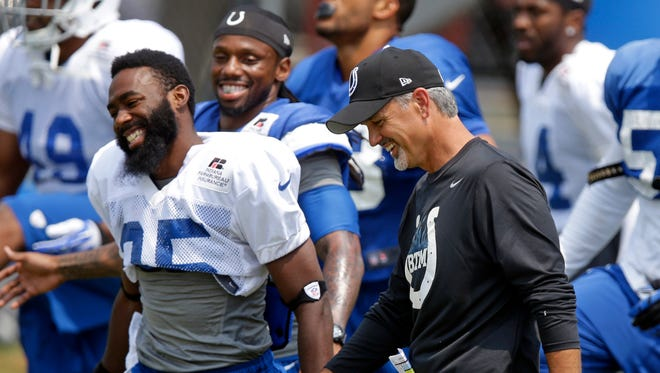 Indianapolis Colts head coach Chuck Pagano, right, laughs with running back Chris Rainey during an NFL football training camp in Anderson, Ind., Saturday, July 26, 2014.