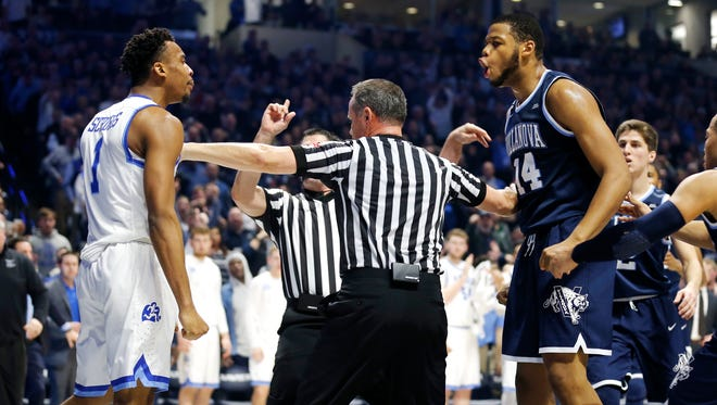 Officials break up Xavier Musketeers guard Paul Scruggs (1), left, and Villanova Wildcats forward Omari Spellman (14) in the 2nd half at the Cintas Center Saturday Feb. 17, 2018. Both players got technicals. Xavier lost 95-79.