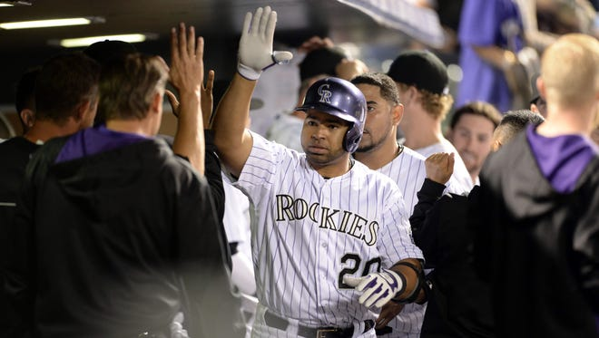 Colorado Rockies catcher Wilin Rosario (20) is congratulated for his home run in the seventh inning against the San Francisco Giants at Coors Field on Tuesday. The Rockies defeated the Giants 5-4.