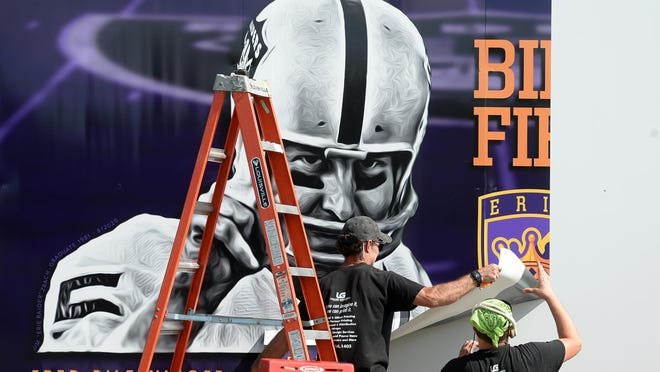 Joe Pepicello, left, and Mike Bush, installers with Erie-based Leader Graphics, install a mural of Erie native Fred Biletnikoff on Friday at Biletnikoff Field at Erie High School.