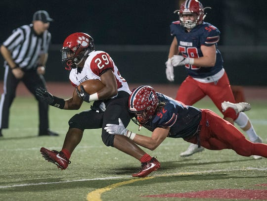 Franklin's Jacb Mass (52) brings down Grand Blanc ball carrier Kettrell Ware Jr (29) during a game this season. Mass was selected to the All-KLAA Gold Division team.