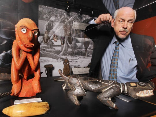 "Robert Genheimer, George Rieveschl curator of Archeology at Cincinnati Museum Center, with a wood and paint figure (left) from Papua, New Guinea, one of the artifacts collected by Julius and Dorette Fleischmann during a round the world trip in 1931-32. The figure was made between 1900-1930 and is Genheimer's favorite in the collection. It is part of the Cincinnati Museum Center's ""Treasures of Travel: Cincinnatians Collect the World."""