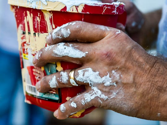 Paint dries on the hand of one of the volunteers who