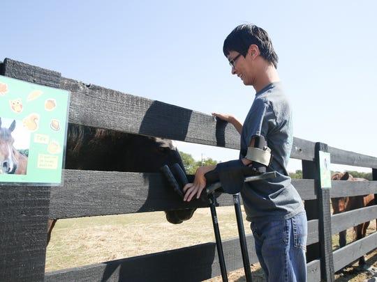 Saddle Up! rider FuXia Caudill pets Tex the horse at