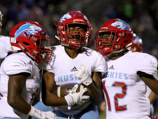 Hirschi's Mychal Lee, left, Nate Downing and Stavonte Vaughn celebrate Downing coming up with the Decatur fumble Friday, Oct. 20, 2017, in Decatur at Eagles Stadium.