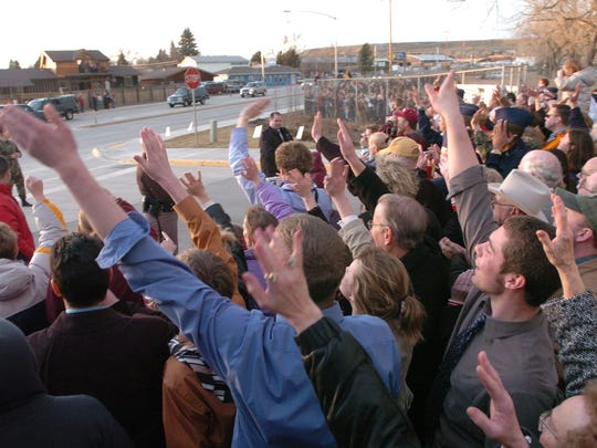 A group waves as the president's motorcade drives down 6th Street Northwest as it heads for the Great Falls International Airport on Gore Hill. Bush's flight departed Great Falls about 5:30 p.m. Thursday, Feb. 3, 2005.