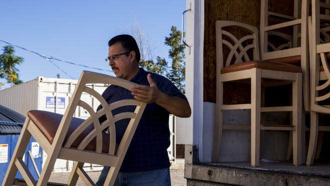 Felipe Jimenez unloads a chair at the Bridging Arizona Warehouse on Oct. 31, 2015 in Mesa. Bridging Arizona Furniture Bank supplies furniture to people transitioning from shelters and group homes.