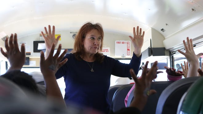 Lynn Roy, a bus driver for George Welch Elementary School, asks a group of first graders to hold up ten fingers during a talk about how to act safely on and around a school bus during Safety Town on Tuesday. Roy told students that they need to be ten feet in front of or behind a school bus before they cross the street or walk around it. She then took students outside to walk around the bus so they would know what that distance looked like.