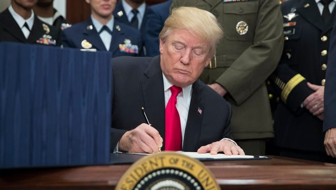 President Trump signs the National Defense Authorization Act for Fiscal Year 2018, beside military personnel in the Roosevelt Room of the White House in Washington Tuesday.