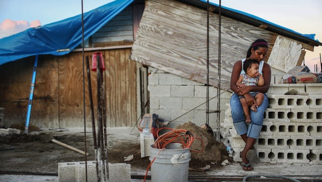 Mother Isamar holds her 9-month-old baby Saniel outside their makeshift home in San Isidro, Puerto Rico, on Dec. 23, 2017, after being mostly destroyed by Hurricane Maria.