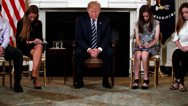President Trump bows his head during an opening prayer at the start of a listening session with high school students and teachers in the State Dining Room of the White House in Washington, Wednesday, Feb. 21.