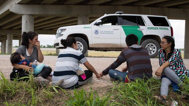 Migrant families from Honduras & Guatemala wait to be taken to a processing center by U.S. Border Patrol agents.