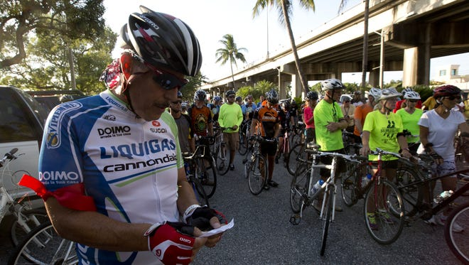 Ray Vega reads a poem along with other cyclists before the Ride of Silence in Fort Myers on Wednesday 5/21/2014.  The ride honors those that have been killed or injured while riding.   Vega is wearing the red arm band because he was was injured after being hit by a vehicle and thrown from his bike.