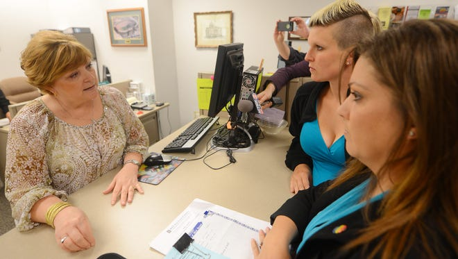 Brown County Clerk Sandy Juno, left, explains her reasons for not accepting the marriage license application from Berri West, center and Lisa West, right, in the clerk's office on June 9, 2014.  The women eventually received a marriage license and were wed.