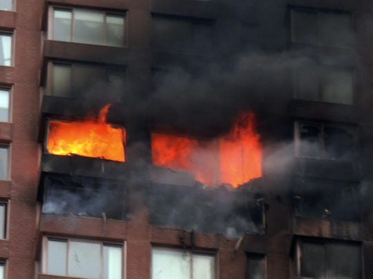 Flames are seen coming out windows where a small plane piloted by pitcher Cory Lidle crashed into a 50-story residential apartment building in New York's Upper East Side on Wednesday, Oct. 11, 2006.