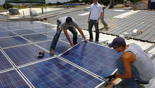 Clayton Lane, center, of James Lane Air Conditioning, oversees the installation of a solar energy system atop the business in 2010. Lane reported on the savings of that and other efficiency upgrades during a Back to Business Wednesday program at MSU.