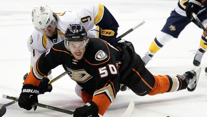 Ducks forward Antoine Vermette and Predators forward Filip Forsberg fall to the ice as they fight for the puck.
