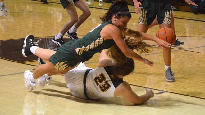 Zeeland West's Marcy Creevy (top) dives for a loose ball against Zeeland East last season.