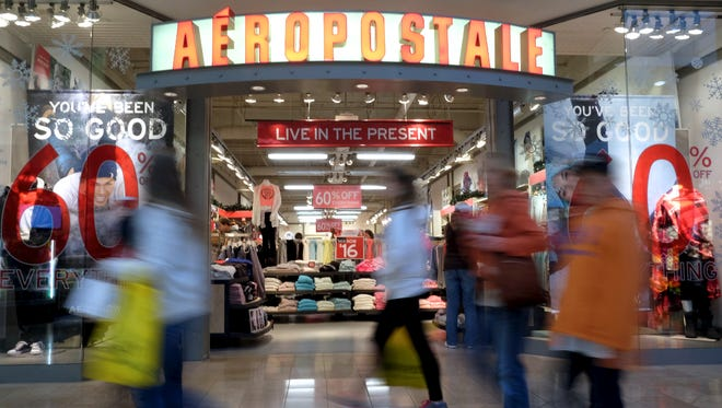 Aeropostale displays 60 percent off signs while shoppers pass by during Black Friday at West Town Mall on Nov. 28, 2014.