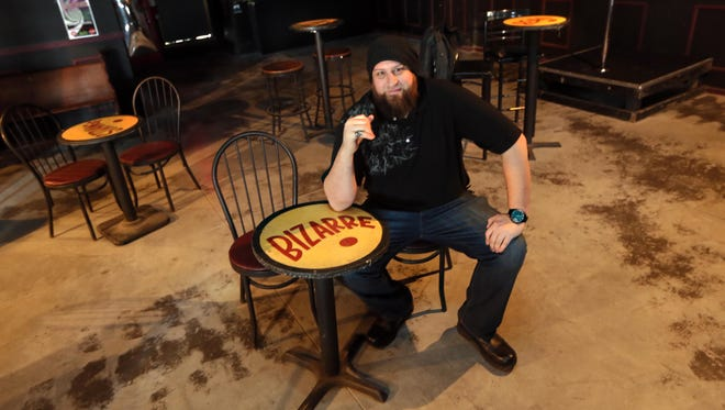 Mojo 13 co-owner Matthew Jester sitting at a table on the new dance floor that has been added to the Holly Oak rock club.
