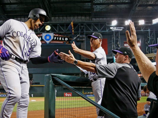 Colorado Rockies' Carlos Gonzalez (5) shouts as he celebrates his two-run home run against the Arizona Diamondbacks with manager Bud Black, third from right, bench coach Mike Redmond, second from right, and pitching coach Steve Foster during the seventh inning of a baseball game Tuesday, Sept. 12, 2017, in Phoenix. (AP Photo/Ross D. Franklin)
