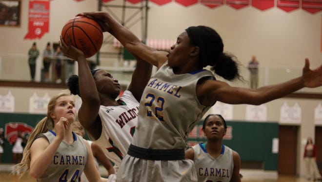 Carmel's Tomi Taiwo blocks a shot in the Greyhounds' win over Lawrence North on Tuesday night.