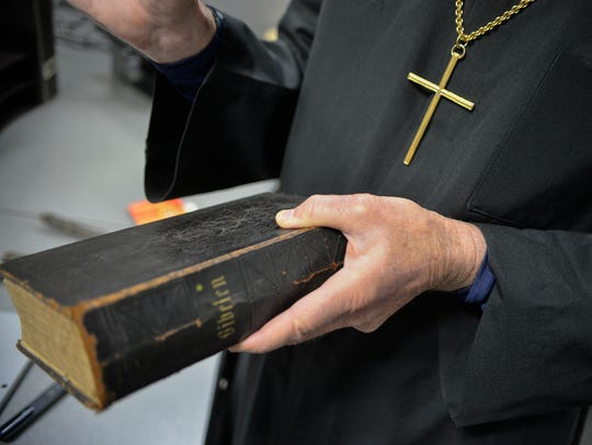 Rev. Larry Strenge holds a German bible while speaking