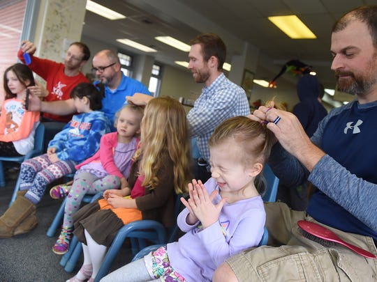 Sophia Amspacher, 4, reacts as her daddy, Erik, puts her hair in a ponytail during the Daddy Daughter Hair Boot Camp in Glatfelter Memorial Library on Saturday, March 25, 2017.