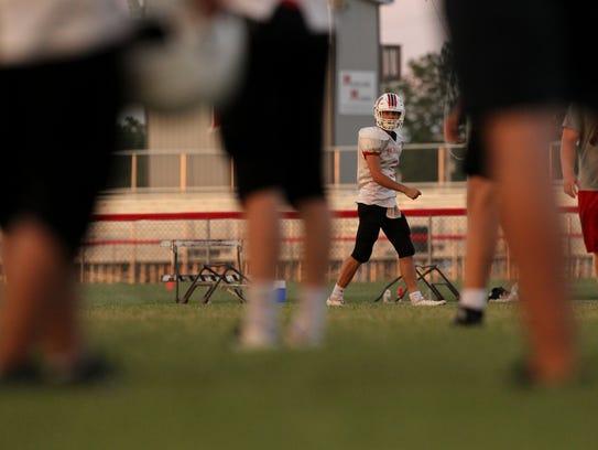 Highland's Trey Lasek runs plays with teammates during