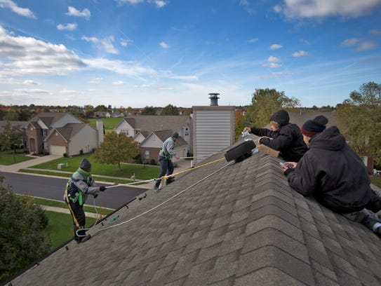 Members from Green Alternatives Inc. install a solar